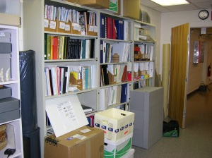 The conservation reference library.  Boxes in front contain duplicates, slanted board is a control mock-up for a Butvar consolidation test.