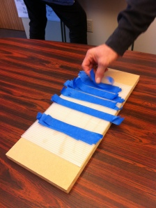 For packing, blue tape with a tab on the end is nice.  Ready to pull off a plastic board (Coroplast) even nicer.  Weighted down by a board so you can use it one-handed!
