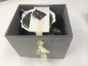 Box with tie-down for the lid of a container.  Tyvek between lid and vessel is a visual cue.