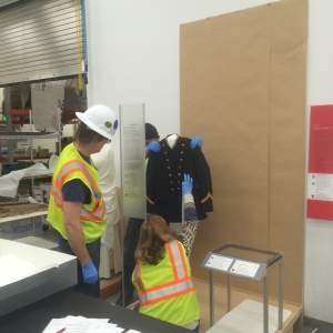 Jackie measures Kow.ee's police uniform while registrar Andrew Washburn holds it up.  Hardhats and loud vests are due to the collections storage and processing areas being in the middle of an active construction zone.  In order to access the site, we are required to wear protective gear.