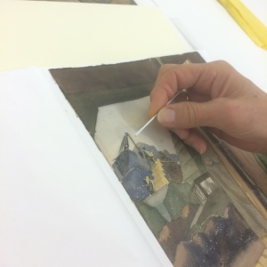 In this image, paper conservator Karen Zukor is examining and testing a watercolor painting from 1943 Adak Island by Warren Beach.  The artwork has some severe spotty staining on the back that is beginning to show through to the front.  A later to posting will detail some of our strategies to control light levels in the upcoming exhibits.