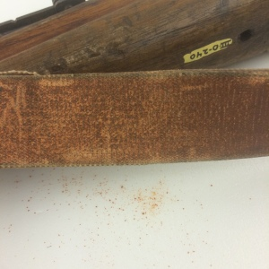 The strap of the rifle is actively flaking an orange powder.  This material will need to be characterized and stabilized before it can go on display.
